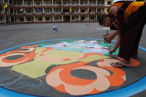 A monk paints Buddhist symbols at Namdroling Monastery in Bylakuppe, India