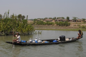 A boat carries urns of drinking water along a river in the Sundarbans. Photo: Amy Yee