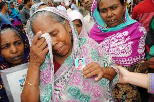Two years after the collapse of the factory at Rana Plaza, families of victims gather, holding photos of their lost loved ones. (Amy Yee for NPR)